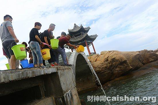 祈福法会信众在南山小月湾海边放生鱼苗